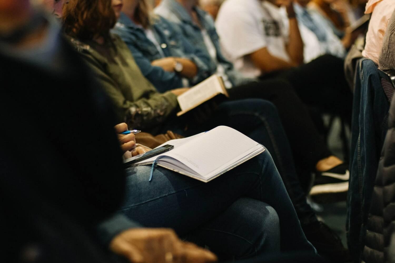 Tagungsgäste sitzen im Publikum und machen Notizen.